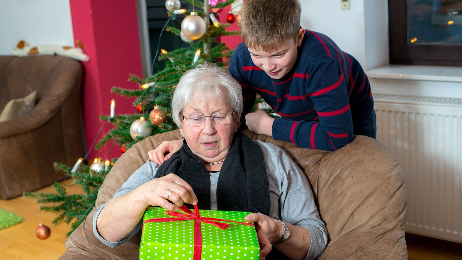 Grandmother opening a gift from her grandson.
