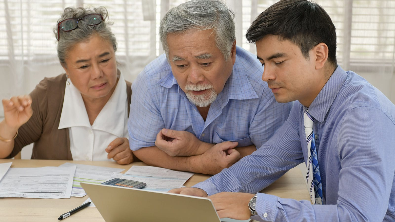 Financial consultant assisting senior couple with their taxes.