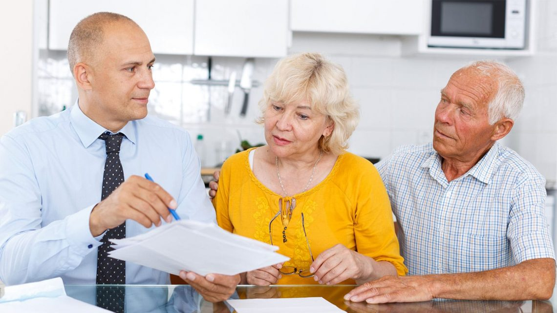 Personal Finance Manager assisting senior couple with their financial organization.